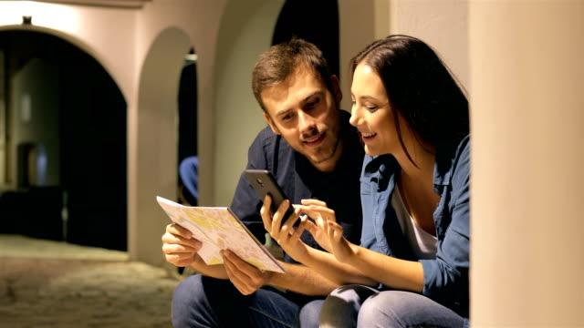 couple of tourists checking phone in the night on holiday - fare una prenotazione video stock e b–roll