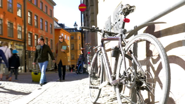 Couple of tourists walking around the city Steadicam shot of young couple of travelers walking in European street with parked bikes. View to the house and sky with bright sun at the end stockholm stock videos & royalty-free footage