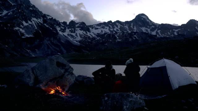 par av resenärer i skymningen nära en lägereld - bål utomhuseld bildbanksvideor och videomaterial från bakom kulisserna