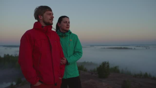 stockvideo's en b-roll-footage met aantal reizigers voldoet aan de zonsopgang in de bergen - men blazer