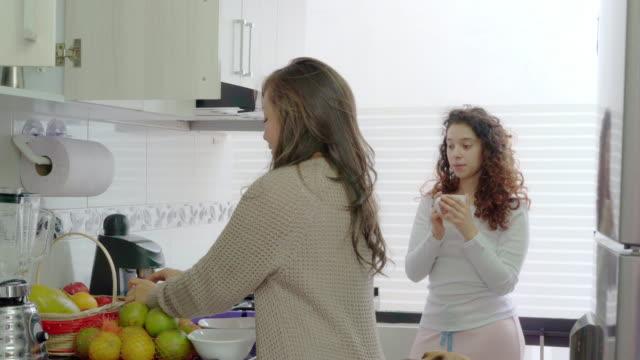 Couple of women LGBTQ preparing an orange juice