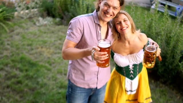 A couple of young people at the Oktoberfest festival drink beer from big glasses. The girl is dressed in a national Bavarian costume video