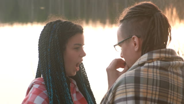 Couple of young people: man and woman eats meat on the riverbank at sunset. Romantic evening together. Girl with plaits in her hair, a young man with dreadlocks. Couple of young people: man and woman eats meat on the riverbank at sunset. Romantic evening together. Girl with plaits in her hair, a young man with dreadlocks blue hair stock videos & royalty-free footage
