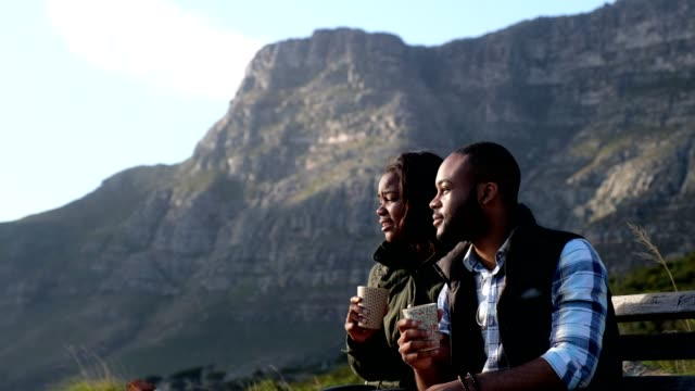 Couple on a hike enjoy a coffee break overlooking the city