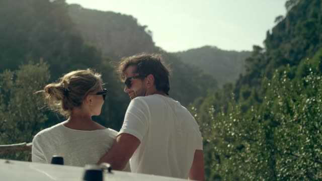 Couple on a road trip. Enjoying the view during break Young couple having break during road trip. Enjoying sun and view young couple stock videos & royalty-free footage