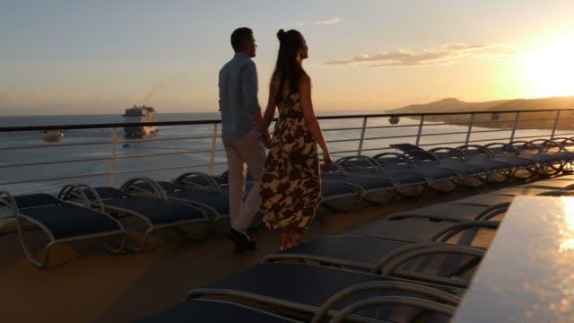 Couple on a romantic sunset walk on a cruise ship