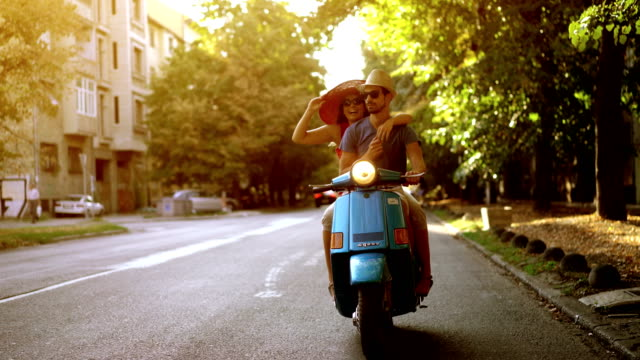 couple on a scooter bike driving through city streets. - ventenne video stock e b–roll