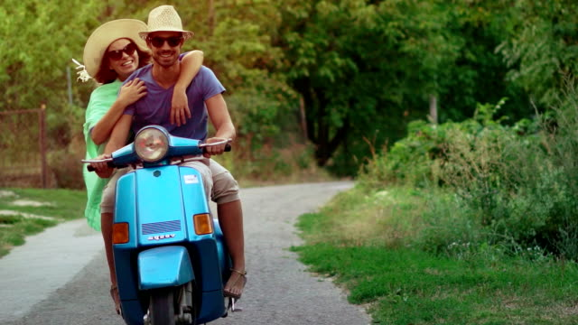 Couple on a scooter bike driving through country area. video