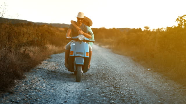 Couple on a scooter riding through a countryside. Closeup front view of mid 20's couple cruising on a scooter bike through coutryside landscapes. They are enjoying the ride and doing some sight seeing. 4k love emotion stock videos & royalty-free footage