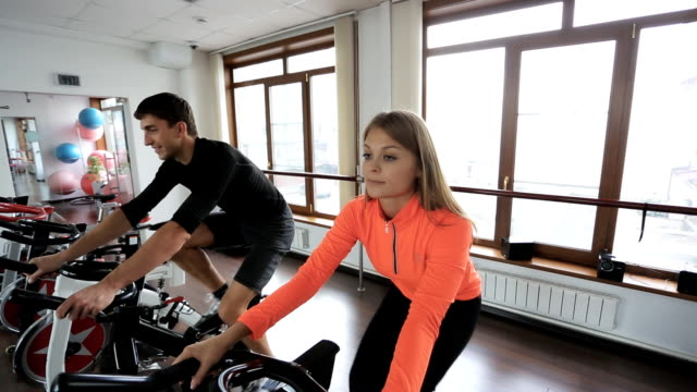 Couple on a stationary bike at gym with big windows