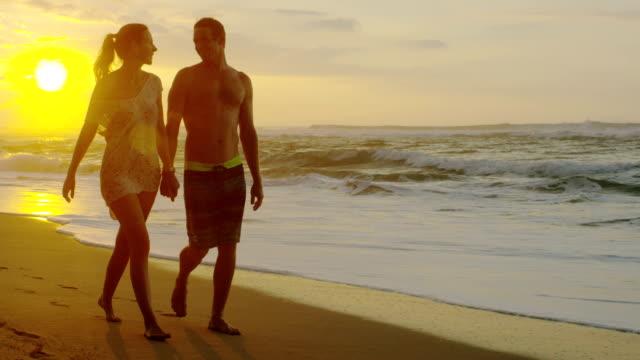 coppia su una spiaggia tropicale alle hawaii per una luna di miele vacanza - due genitori video stock e b–roll