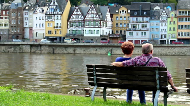 Couple on bench sitting on quay German village river, buildings. Beautiful shot of Europe, culture and landscapes. Traveling sightseeing, tourist views landmarks of Germany. World travel, west European trip cityscape, outdoor shot video