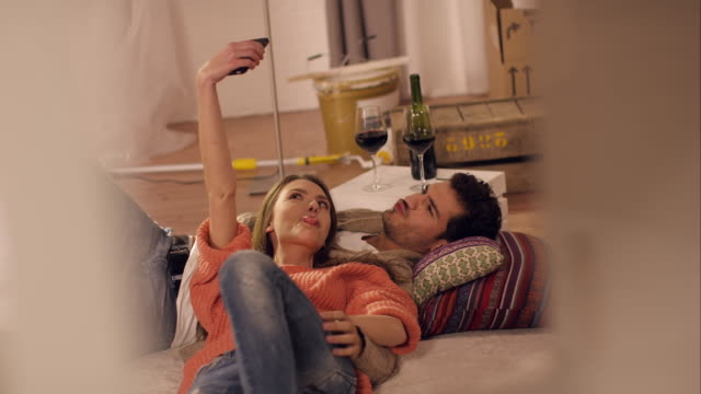 Couple on carpet taking selfies in new apartment video