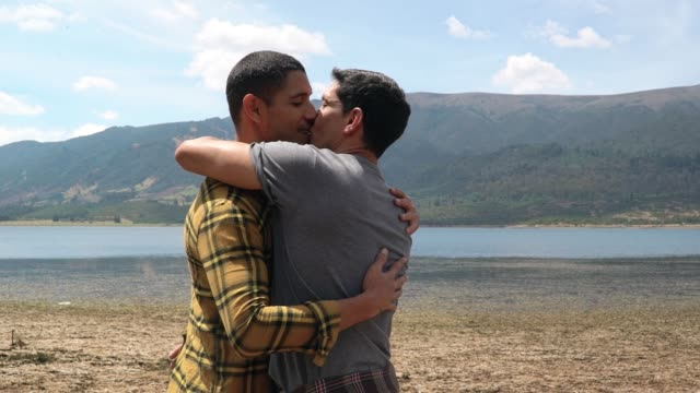 LGBT couple on holidays Latin gay couple enjoying a holiday while they kissing in front of the lake in the mountain. (slow motion) gay man stock videos & royalty-free footage