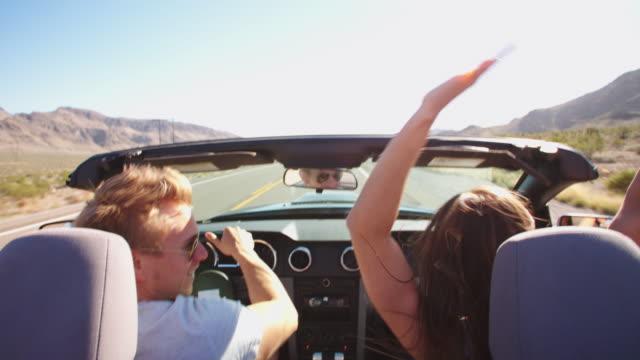 vidéos et rushes de couple en voyage voiture décapotable conduite de tir sur r3d - homme faire coucou voiture