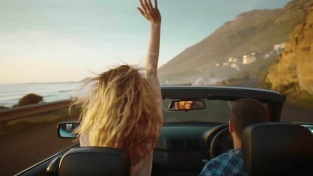 Couple on road trip with convertible driving along coast at sunset