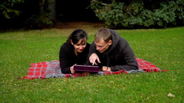 couple on the grass with tablet - compagni scuola video stock e b–roll
