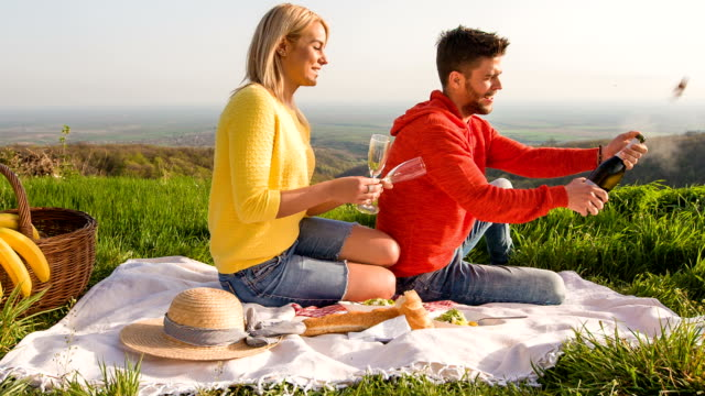 Couple opening a bottle of wine during picnic Happy young couple opening a bottle of wine while having a romantic picnic in nature. aperitif stock videos & royalty-free footage