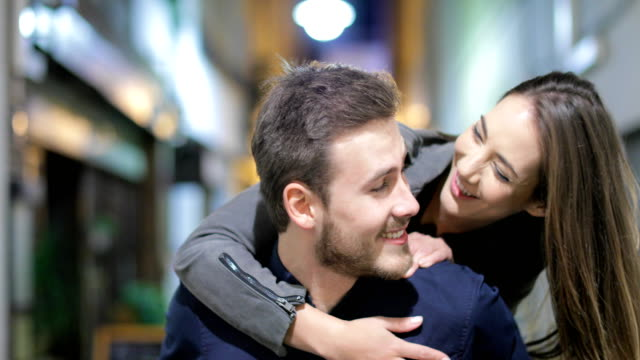 Couple or friends joking in the night in the street Front view of a happy couple or friends walking meeting and joking in the night in the street falling in love stock videos & royalty-free footage