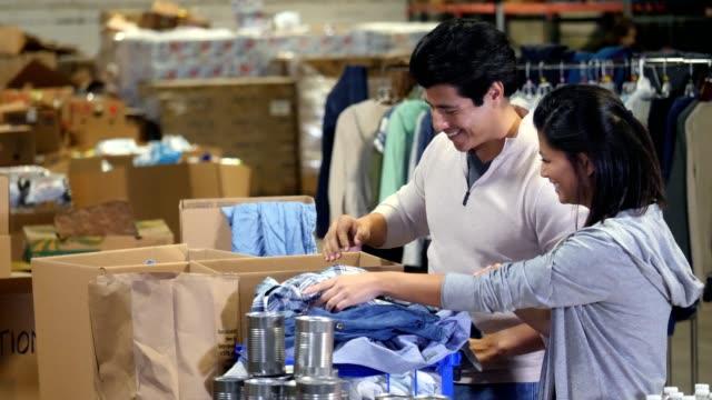 vídeos y material grabado en eventos de stock de un par organizar y doblar ropa donaciones juntos - food drive