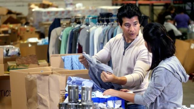 vídeos de stock, filmes e b-roll de casal organiza a roupa juntos durante o trabalho de caridade e alívio - vestuário