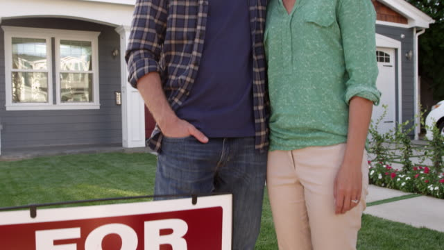 Couple Outside Home With For Sale Sign Shot On R3D video