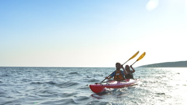 Couple paddling at sea in their red touring kayak on a sunny day