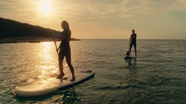 Couple paddling on their SUPs at sunset video