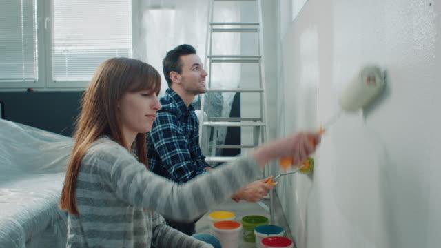 vídeos de stock, filmes e b-roll de casal pintando paredes em sua nova casa - decoração