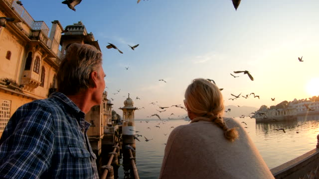 couple pause above lake and floating palace at sunrise - guardare il paesaggio video stock e b–roll