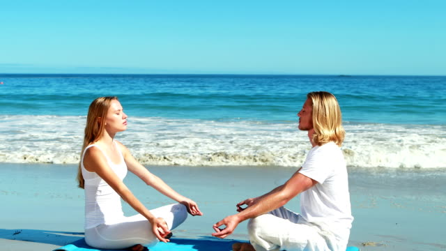 Couple performing yoga at beach Couple performing yoga at beach on a sunny day face to face stock videos & royalty-free footage