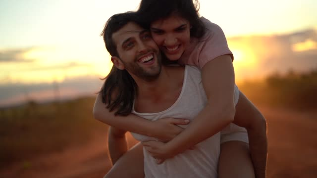 Couple piggyback at road trip on sunset time