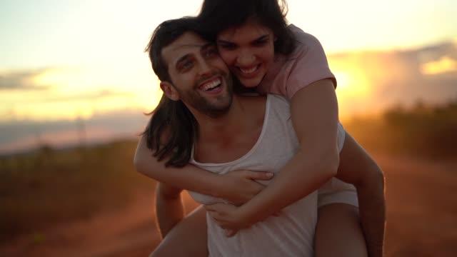 gün batımı nda yol gezisinde çift piggyback - flört etmek stok videoları ve detay görüntü çekimi