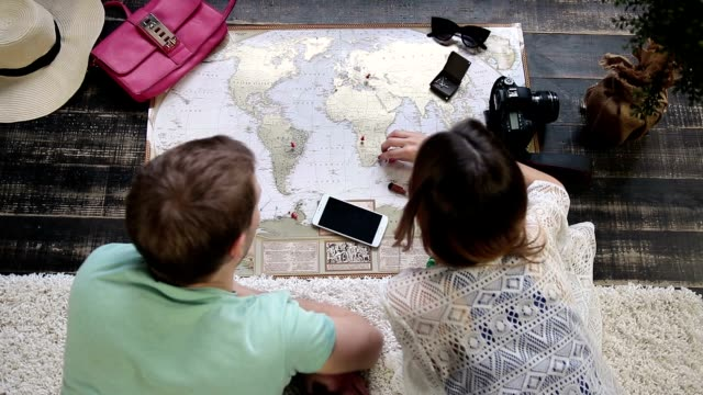 couple planning new journey with travel map - progettare video stock e b–roll