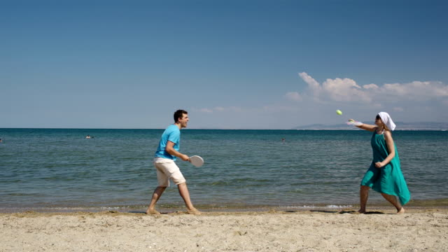 Couple playing bat and ball at the beach video
