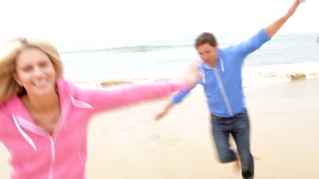 Couple Playing On Fall Beach Together video