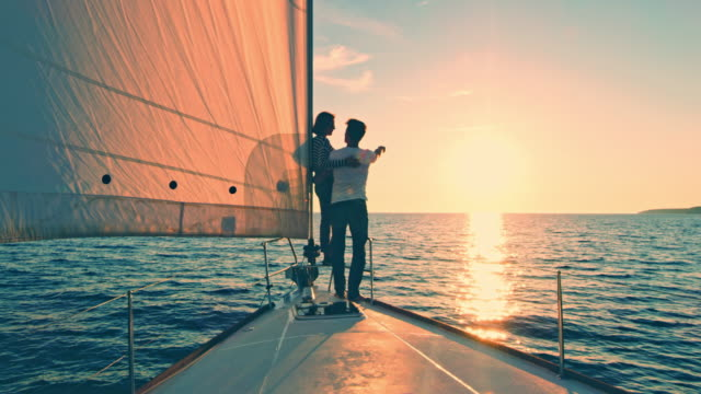 vídeos de stock e filmes b-roll de ws couple pointing at the horizon from a sailboat at sunset - veleiro