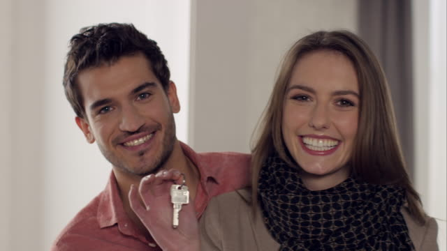 Couple posing with key in new apartment