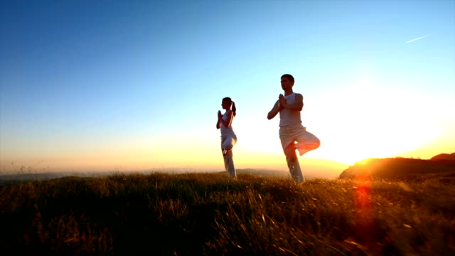 couple practicing yoga at sunset - mindfulness 個影片檔及 b 捲影像