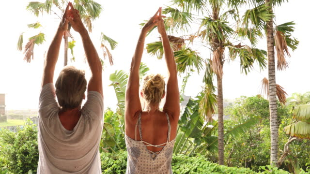Couple practise yoga moves in tropical setting video