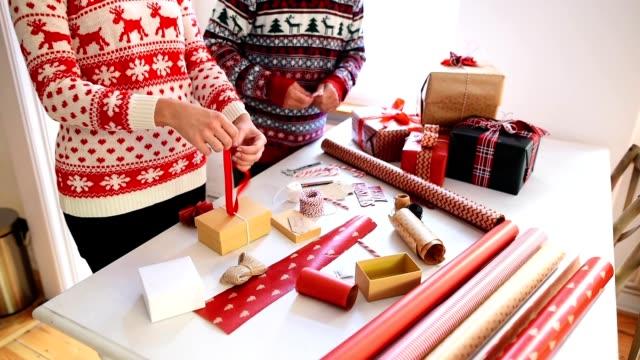 couple preparing the packages for christmas - avvolgere video stock e b–roll