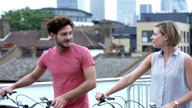 Couple Pushing Bikes With City Skyline In Background video