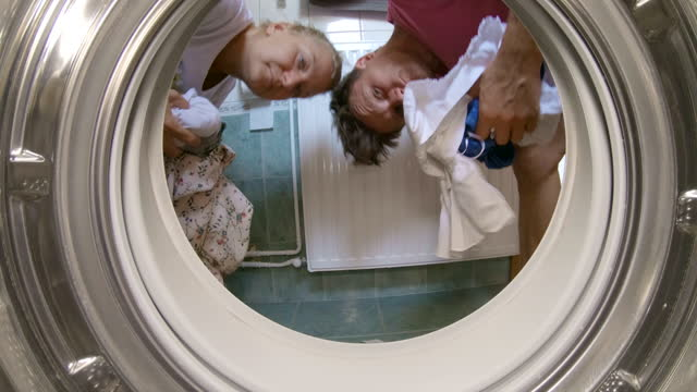 Couple putting dirty clothes into the washing machine