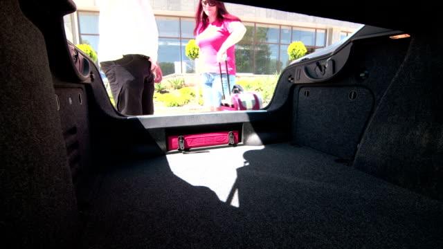 vidéos et rushes de couple faisant vos valises dans coffre de voiture pour voyage d'été - wagon