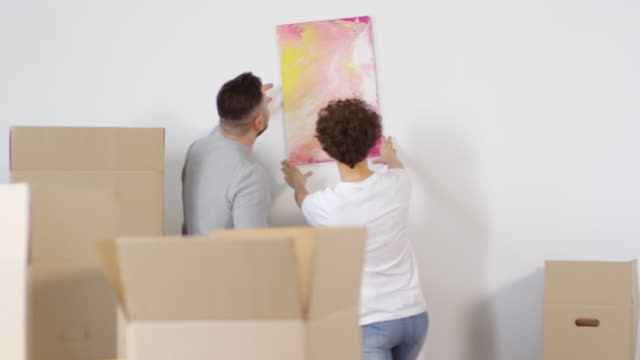Couple Putting Up Painting on Wall Together in First Home