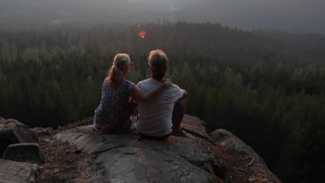 vidéos et rushes de couple se détendre au-dessus des forêts et des montagnes au lever du soleil - évasion du réel