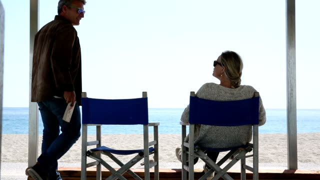 Couple relax on beach chairs with digital tablet, book, at beach - vídeo