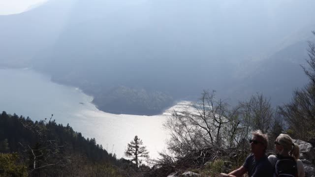 couple relax on bench above lake, valley - tilt down stock videos & royalty-free footage