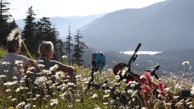 Couple relax with mountain bikes on meadow slope, in flowers