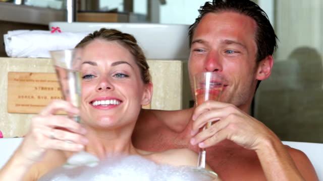 paar entspannenden zusammen im bad trinkt champagner  - champagner toasts stock-videos und b-roll-filmmaterial